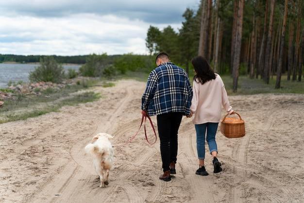 해변에서 강아지와 함께 전체 샷된 사람