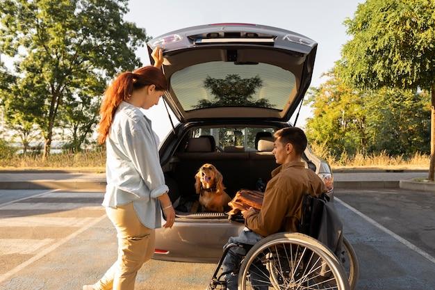Persone a tutto campo con cane e macchina