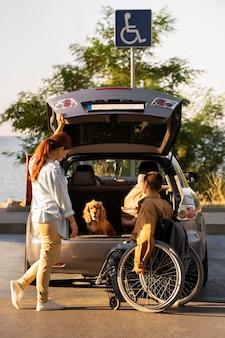 Persone a tutto campo con sedia a rotelle e auto