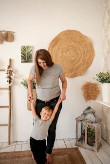Full shot pregnant woman playing with toddler