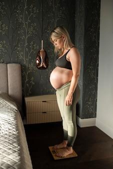 Donna incinta a tutto campo che si pesa