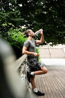 Full shot of runner drinking water