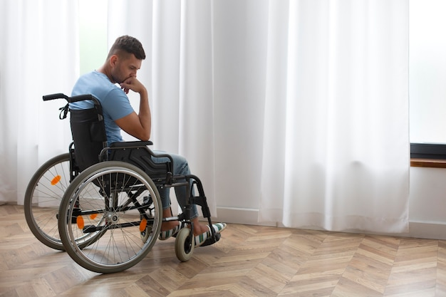 Full shot sad man in wheelchair
