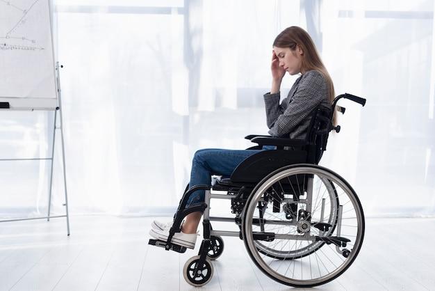 Donna triste della foto a figura intera in sedia a rotelle