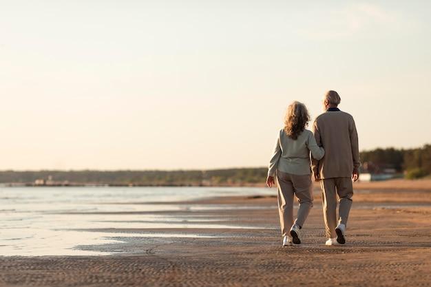 海辺でフルショットの年配のカップル