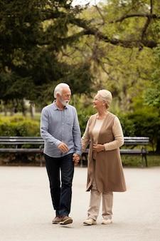 手をつないでフルショットの年配のカップル