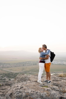Full shot senior couple hugging on cliff