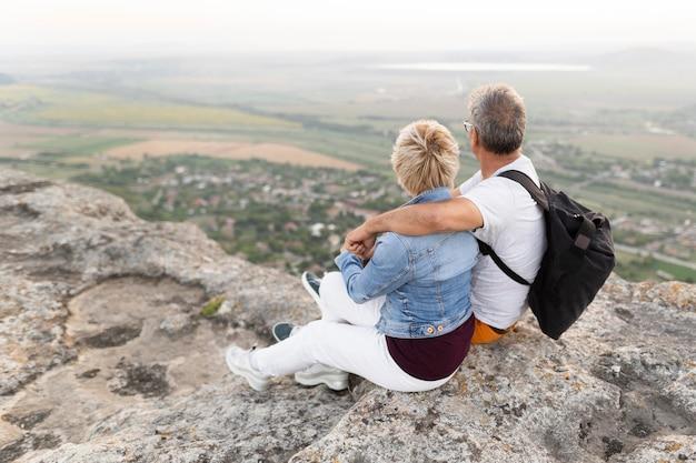 Full shot senior couple sitting on cliff