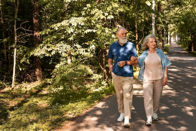 一緒に歩くフルショットの年配のカップル