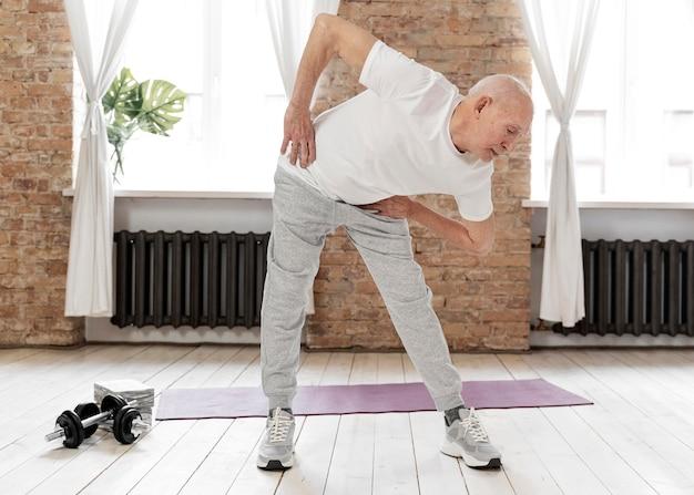 屋内で運動するフルショットの年配の男性