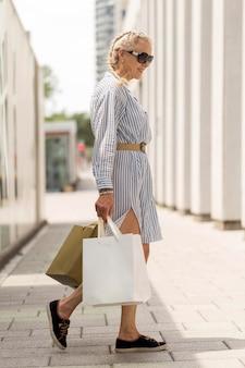 Donna anziana a tutto campo che porta le borse della spesa