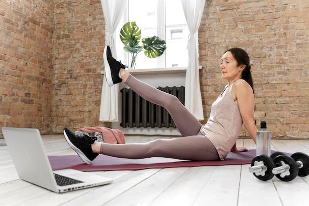 ノートパソコンで運動するフルショットの年配の女性