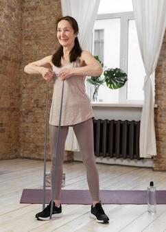 運動するフルショットの年配の女性