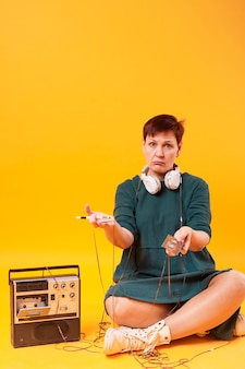 Full shot senior woman holding cassette tape