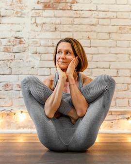 Полный выстрел старшая женщина на коврике для йоги