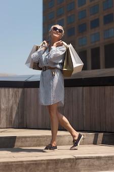 Donna anziana a tutto campo con le borse della spesa