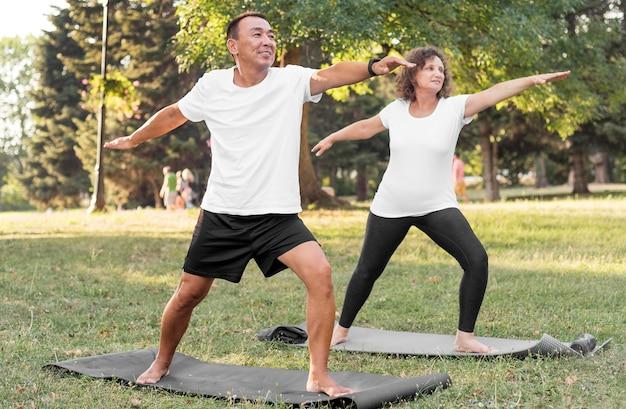 Пожилые люди в полный рост, тренирующиеся на ковриках для йоги