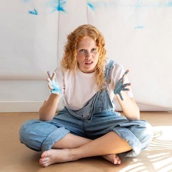 Полный выстрел сидит женщина с нарисованными ладонями