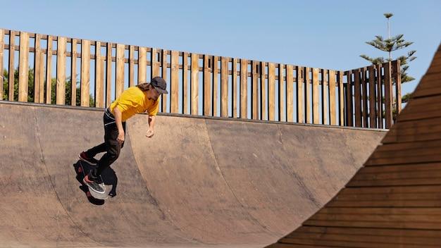 Полный скейтбордист в шляпе