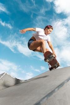 야외에서 보드와 함께 점프하는 전체 샷 스케이팅 선수