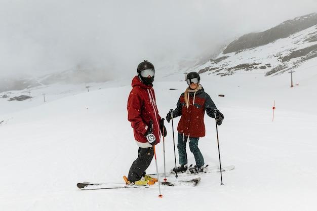 Полные лыжники, стоя на открытом воздухе