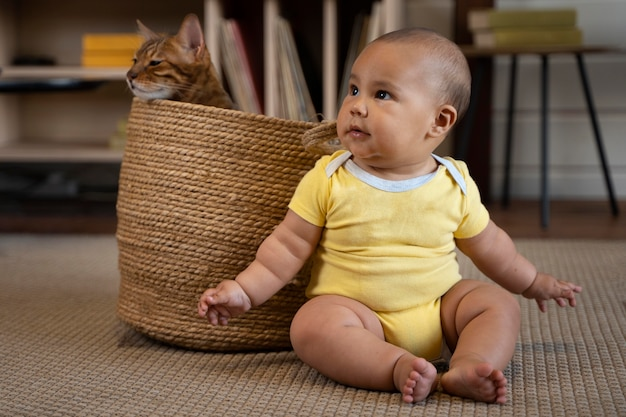 Full shot smiley baby and cat in basket