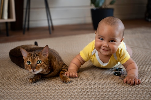Full shot smiley baby and cat on floor