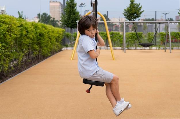 Full shot smiley boy on swing