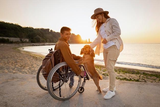 해변에서 강아지와 함께 전체 샷 웃는 커플