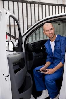 Full shot smiley delivery man in van
