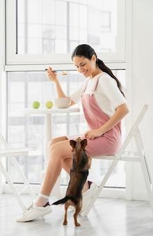 Полный снимок смайлик девушка ест рядом с собакой
