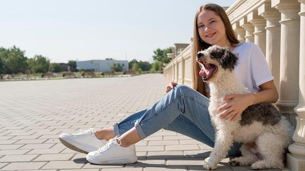 Полный снимок смайлик девушка держит милую собаку
