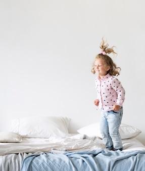 전체 샷 웃는 소녀 침대에서 점프