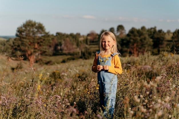 Ragazza sorridente a tutto campo in natura