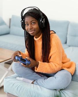 ビデオゲームをプレイするフルショットのスマイリーガール