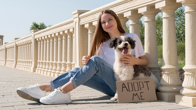 Полный снимок смайлик девушка сидит с милой собакой