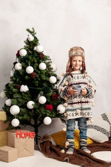 Full shot smiley kid near the christmas tree