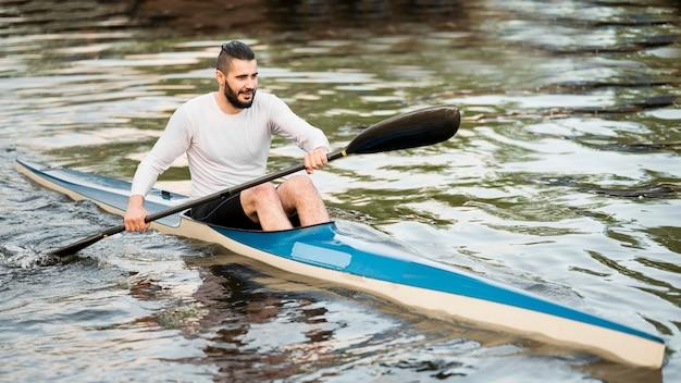 Full shot smiley man holding oar