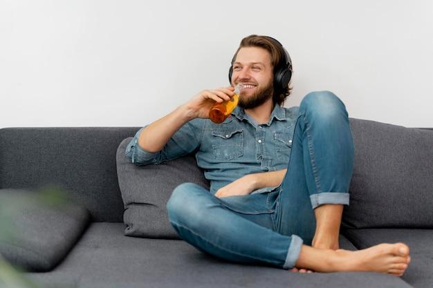 飲み物とヘッドフォンでフルショットのスマイリーマン