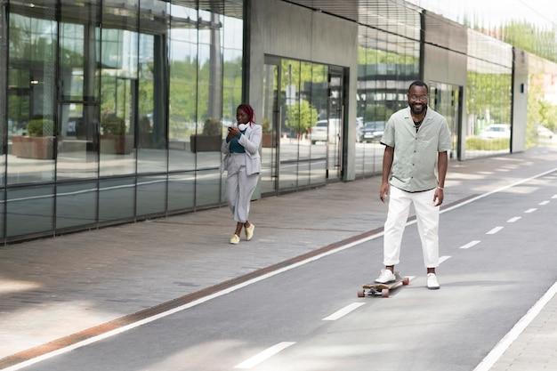 Full shot smiley man with skateboard