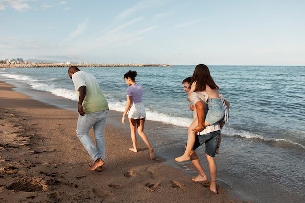 해변에서 전체 샷 웃는 사람들