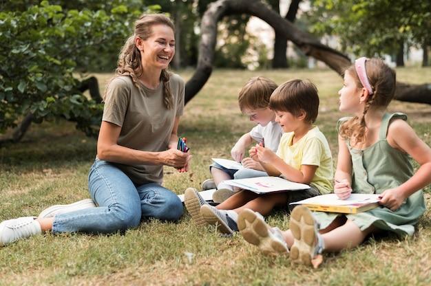 フルショットのスマイリー先生と屋外の子供たち