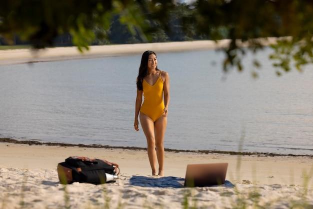 해변에서 전체 샷 웃는 여자