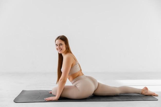 Full shot smiley woman doing the splits