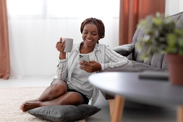 Full shot smiley woman holding phone