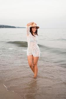 フルショットスマイリー女性が海でポーズ