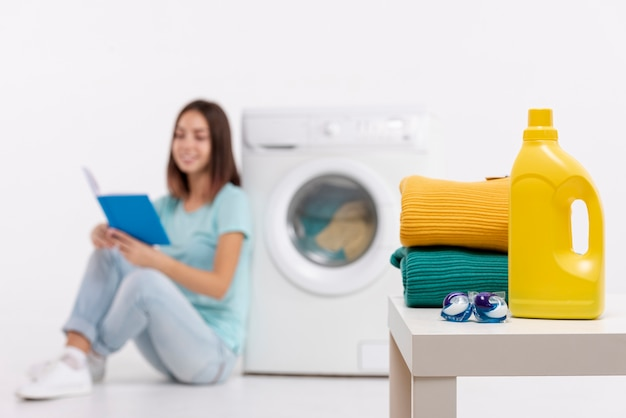Full shot smiley woman reading and doing laundry
