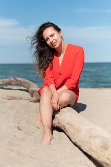 해변에 앉아 전체 샷된 웃는 여자