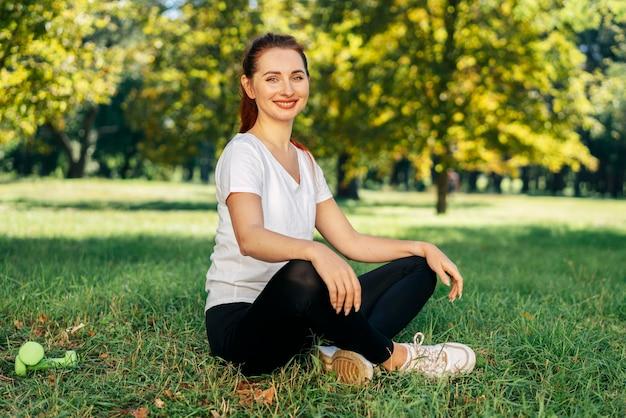 Full shot smiley woman sitting on grass