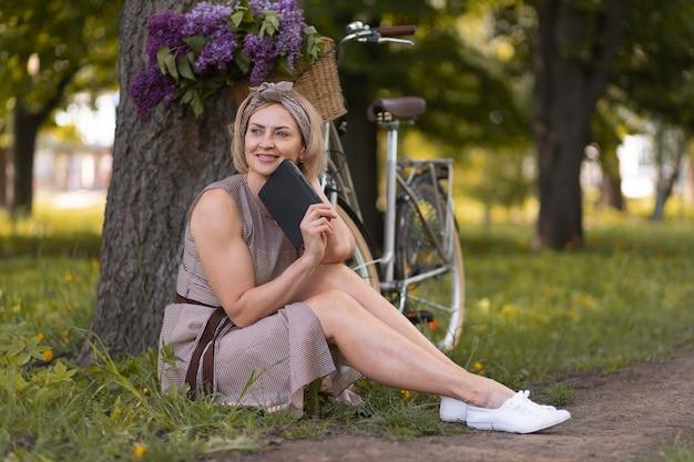 Donna sorridente a tutto campo seduta sull'erba
